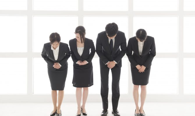 Four Japanese business people bowing at you