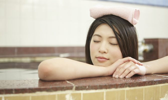 Japanese woman taking a bath with a small towel on top of her head