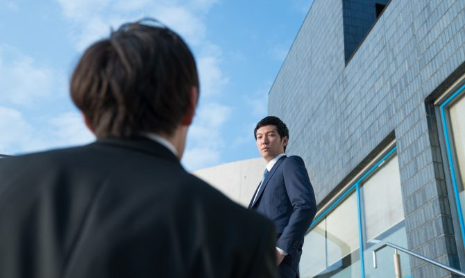 A Japanese businessperson looking down at a junior businessperson