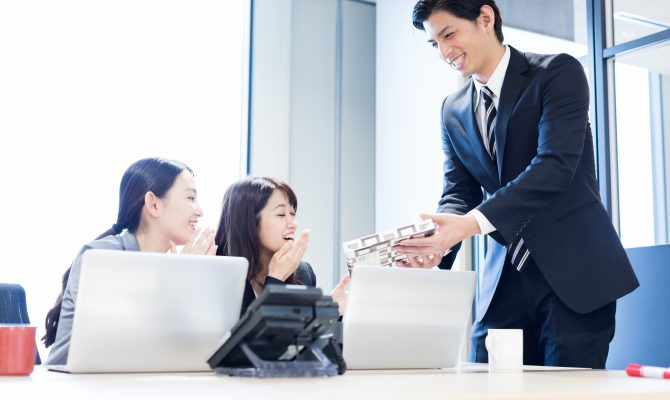 A Japanese Businessman giving omiyage to his colleagues