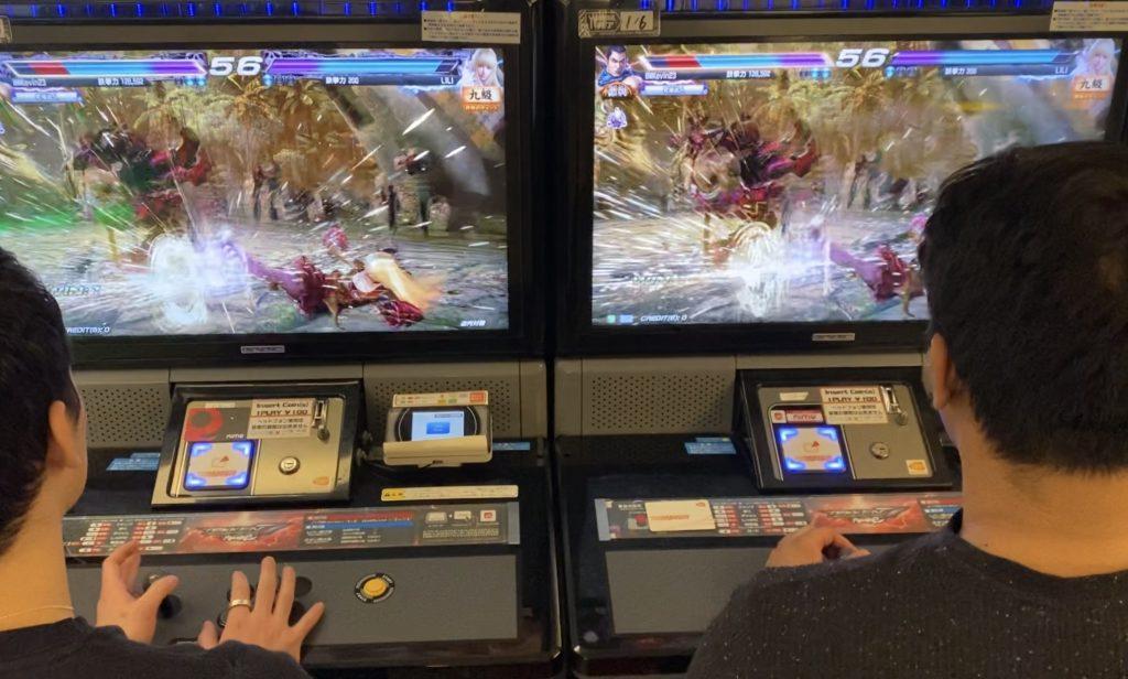 """Two men playing an arcade game """"Tekken"""""""