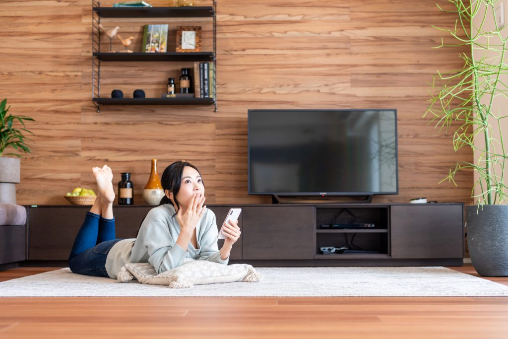 Japanese woman in the living room, wondering what show to watch next.